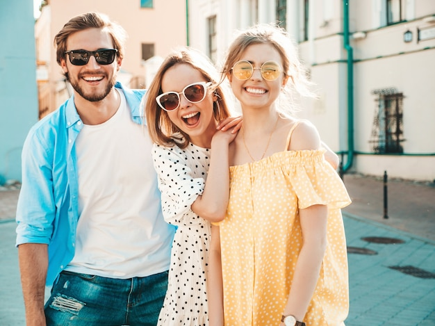 Группа молодых трех стильных друзей позирует на улице. мода мужчина и две милые девушки, одетые в повседневную летнюю одежду. улыбающиеся модели с удовольствием в солнцезащитных очках. веселые женщины и парень в сюзне Бесплатные Фотографии