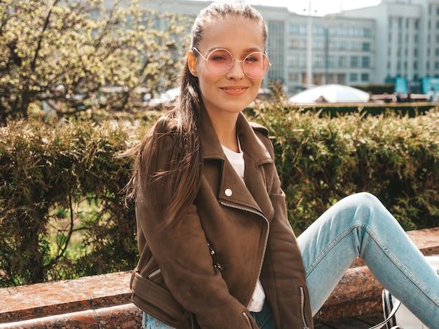 夏の流行に敏感なジャケットとジーンズの服に身を包んだ美しい笑顔ブルネットモデルの肖像ストリートのベンチに座っているトレンディな女の子 無料写真