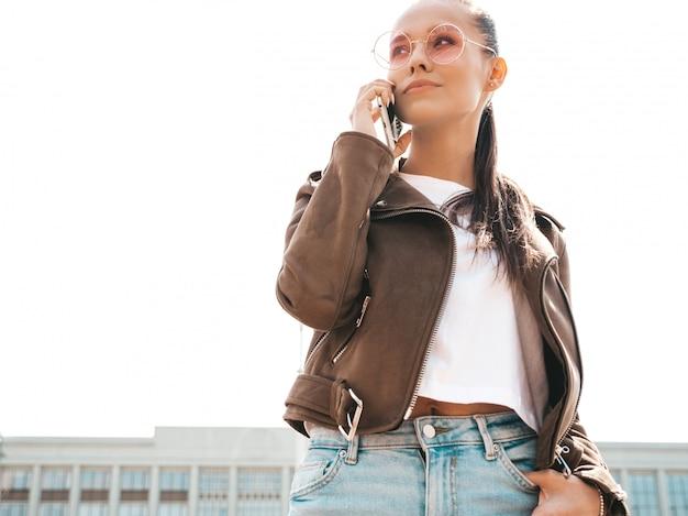 Портрет молодой красивой женщины, говорящей по телефону модная девушка в повседневной летней одежде серьезная женщина позирует на улице Бесплатные Фотографии
