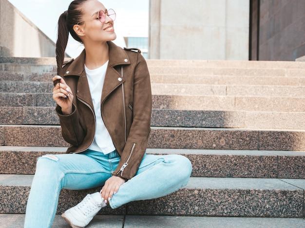 夏の流行に敏感なジャケットとジーンズの服に身を包んだ美しい笑顔ブルネットモデルの肖像画。通りの背景の手順の上に座ってトレンディな女の子。ラウンドサングラスで面白いと肯定的な女性 無料写真