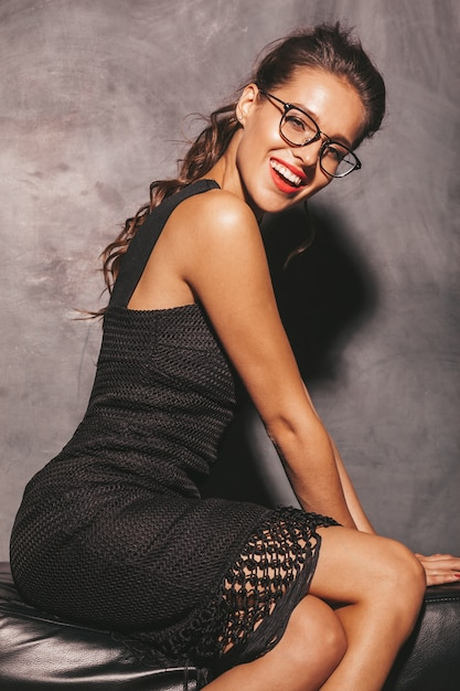 トレンディな夏の黒いドレスの若い美しい流行に敏感な女性の肖像画。セクシーな屈託のない女性が壁に近いポーズします。メイクや髪型とブルネットのモデル 無料写真