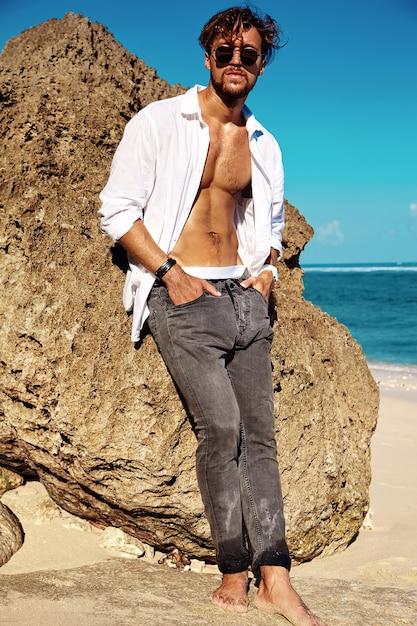 青い空に夏のビーチの岩に近いポーズのメガネで白いシャツの服を着てハンサムな日光浴ファッション男モデルの肖像 無料写真