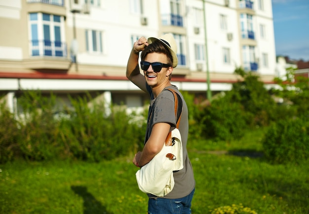 公園でメガネの帽子でカジュアルな布で若い魅力的な笑みを浮かべてモダンなスタイリッシュな男の肖像 無料写真