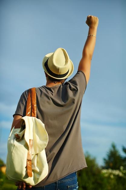 Задняя часть молодого привлекательного современного стильного человека в вскользь ткани в шляпе в очках за голубым небом Бесплатные Фотографии