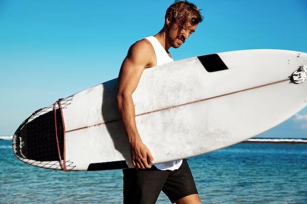 青い海と空にサーフボードで行くカジュアルな服を着てハンサムなヒップスター日光浴ファッション男モデルサーファーの肖像 無料写真