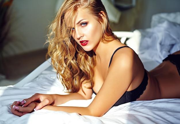 Фасонируйте портрет модели красивой сексуальной молодой взрослой белокурой женщины нося черное эротичное женское бельё лежа на кровати на заходе солнца Бесплатные Фотографии