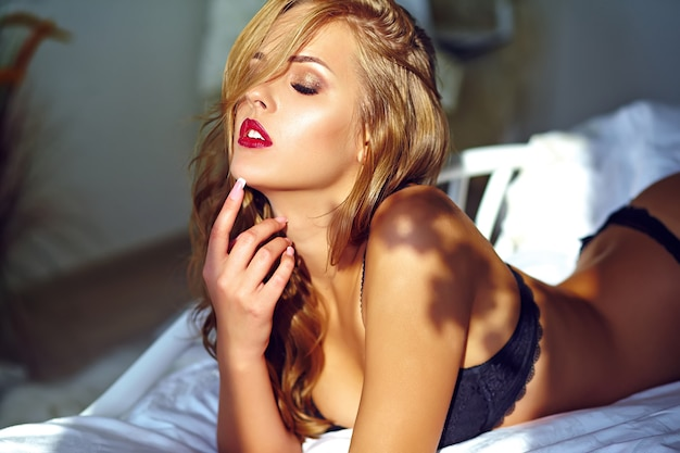夕暮れ時のベッドに横たわっている黒のエロティックなランジェリーを着ている美しいセクシーな若い大人の金髪女性モデルのファッションポートレート 無料写真