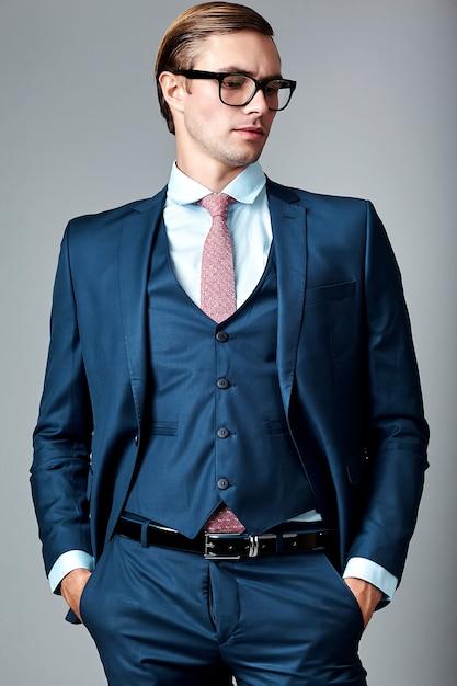 Модель молодого элегантного красивого бизнесмена мужская в голубом костюме и модных стеклах, представляя в студии Бесплатные Фотографии