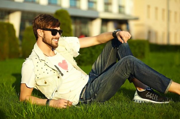 Смешной улыбающийся битник красавец парень в стильной летней одежде на улице в солнцезащитные очки Бесплатные Фотографии