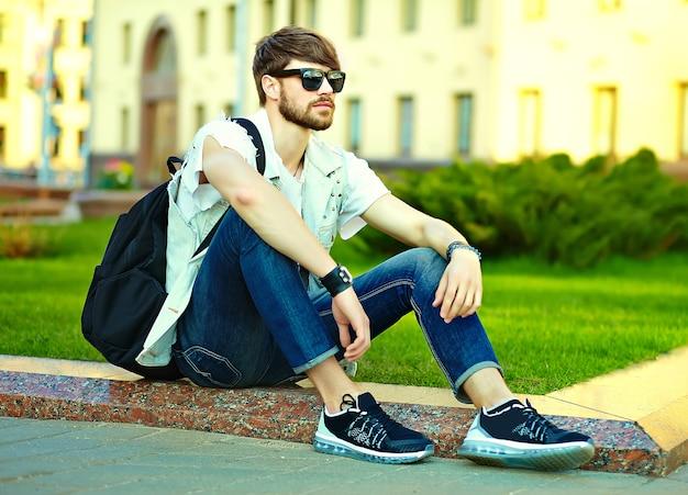 Смешной улыбающийся хипстер красавец парень в стильной летней одежде на улице позирует сидя на траве в темных очках Бесплатные Фотографии