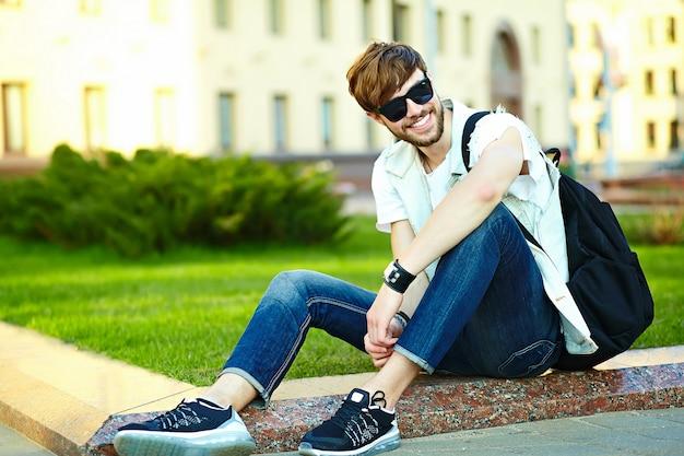公園の芝生の上に座って通りにスタイリッシュな夏布で面白い笑顔ヒップスターハンサムな男男 無料写真