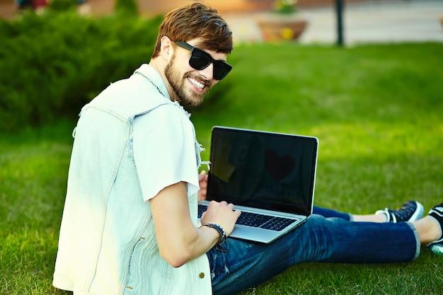 ノートブックと公園の芝生の上に座って通りにスタイリッシュな夏布で面白い笑顔ヒップスターハンサムな男男 無料写真