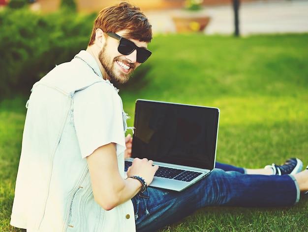 ノートブックと公園の芝生の上に座って通りにスタイリッシュな夏服で面白い笑顔ヒップスターハンサムな男男 無料写真
