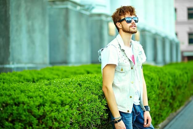 緑豊かな街に近いポーズでスタイリッシュな夏服で面白い笑顔ヒップスターハンサムな男男 無料写真