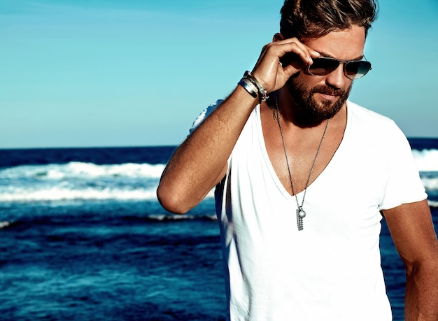 青い海でポーズをとって白い服を着ているハンサムなファッション男モデルの肖像 無料写真