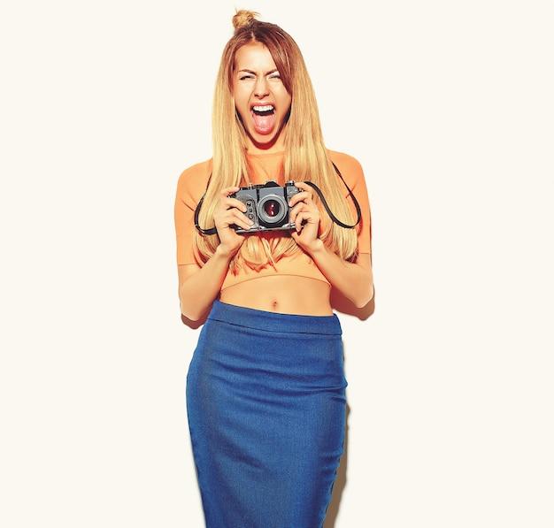 Красивая счастливая милая белокурая женщина девушка в повседневной одежде битник летом принимает фотографии с ретро фотоаппарат, изолированных на белом Бесплатные Фотографии