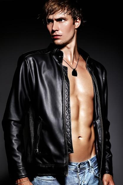 Молодой красивый мускулистый мужчина модель позирует в студии, показывая его мышцы живота в кожаной куртке Бесплатные Фотографии