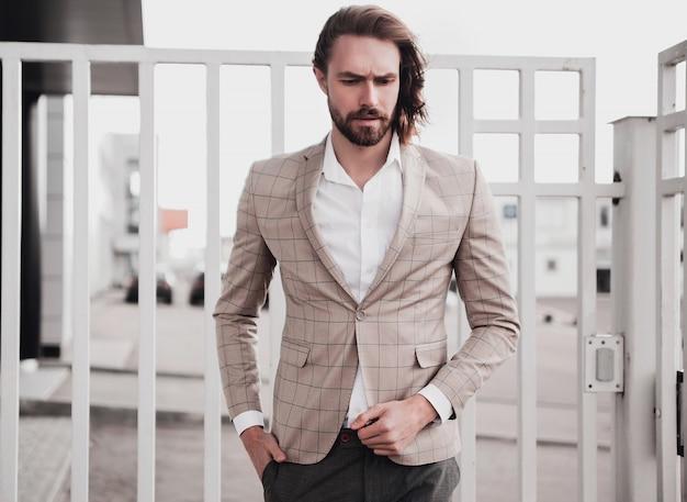 Портрет сексуальный красивый модный мужской модель мужчина одет в элегантный бежевый клетчатый костюм позирует на фоне улицы Бесплатные Фотографии