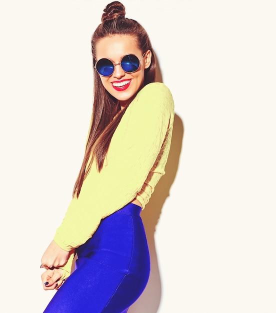 白で隔離される赤い唇とカジュアルなカラフルな黄色の夏服に夢中になって流行に敏感な女の子を笑顔陽気なファッションの肖像画 無料写真