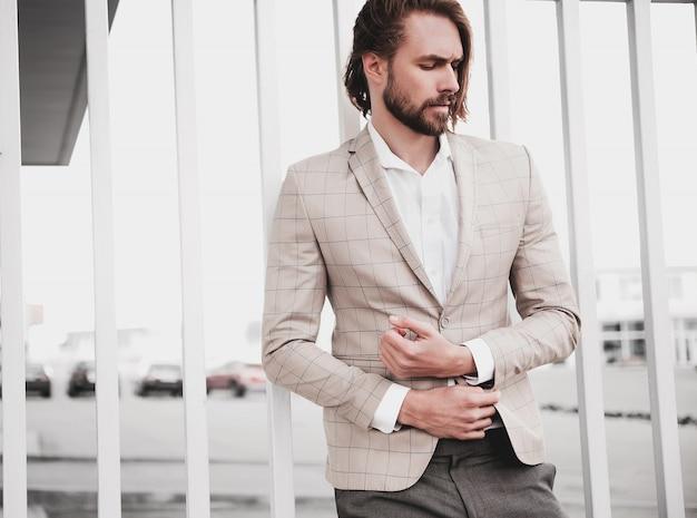 通りの背景にポーズをとってエレガントなベージュの市松模様のスーツに身を包んだセクシーなハンサムなファッション男性モデル男の肖像 無料写真
