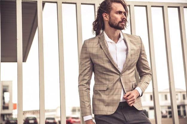 エレガントな市松模様のスーツに身を包んだセクシーなハンサムなファッションビジネスマンモデルの肖像画 無料写真