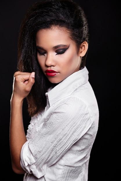白いシャツで明るい化粧赤い唇と美しいアメリカ黒人女性ブルネットの少女モデルのファッションの肖像画。 無料写真