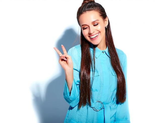 Красивая кавказская усмехаясь модель женщины брюнет в платье яркого голубого лета стильном изолированном на белой предпосылке. показывая знак мира Бесплатные Фотографии
