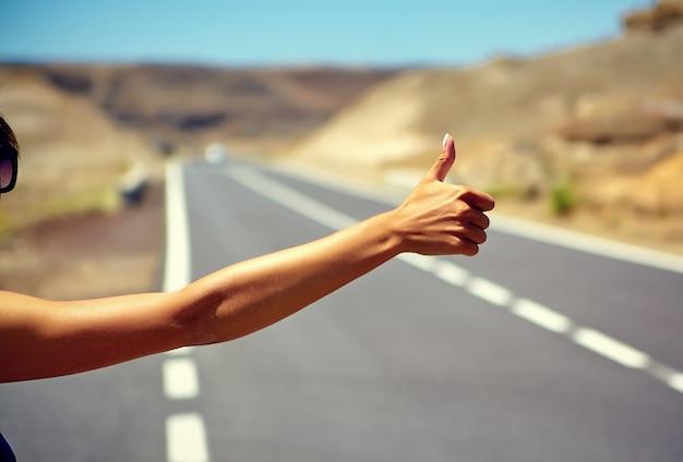 Молодой кавказский турист автостопом по дороге в закат Бесплатные Фотографии