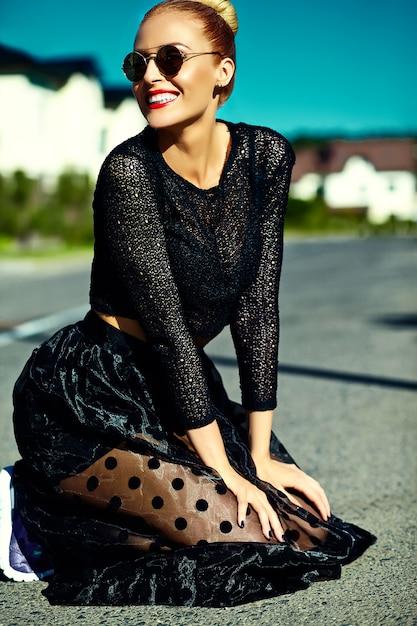 通りに座って夏黒ヒップスター服で面白いスタイリッシュなセクシーな笑顔美しい若いブロンドの女性モデル 無料写真