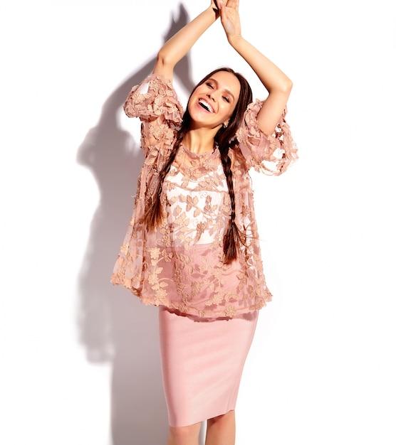 明るいピンクの夏のスタイリッシュな服で二重おさげの美しい白人笑顔ブルネットの女性モデルの肖像画 無料写真
