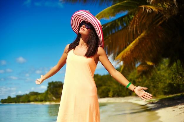 Красивая счастливая женщина в красочной шляпе от солнца и платье, идущем около океана океана в жаркий летний день около пальмы Бесплатные Фотографии