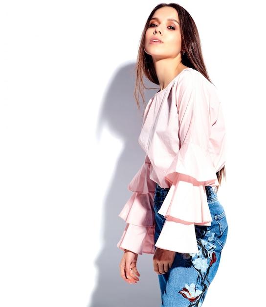Портрет красивой кавказской улыбающейся брюнетки модели в ярко-розовой блузке и летних стильных синих джинсах с цветочным принтом Бесплатные Фотографии