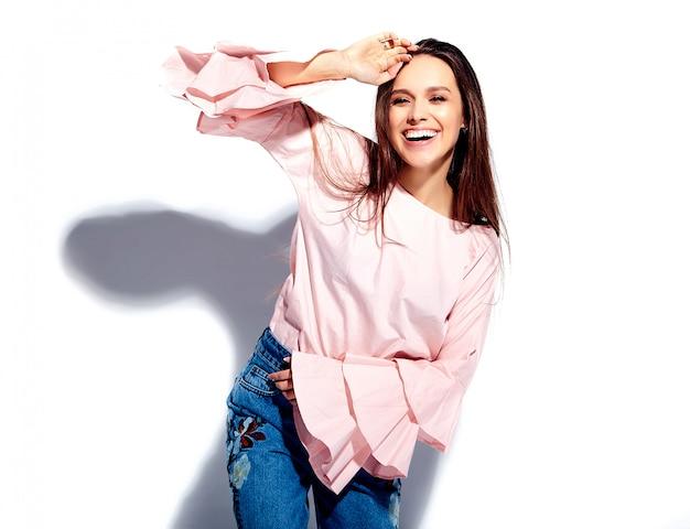 明るいピンクのブラウスと夏のスタイリッシュなブルージーンズで美しい白人笑顔ブルネットの女性モデルの肖像画を印刷 無料写真