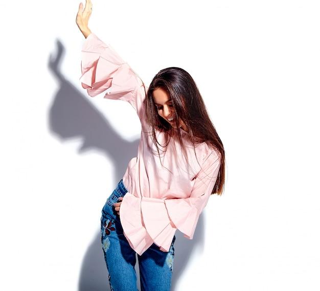 Портрет красивой кавказской улыбающейся брюнетки модели в ярко-розовой блузке и стильных летних синих джинсах Бесплатные Фотографии