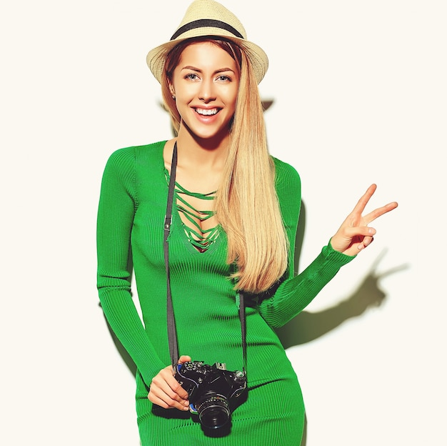 Красивая счастливая милая белокурая женщина девушка в повседневной летней одежде зеленого битника снимает фото с ретро фотоаппаратом Бесплатные Фотографии