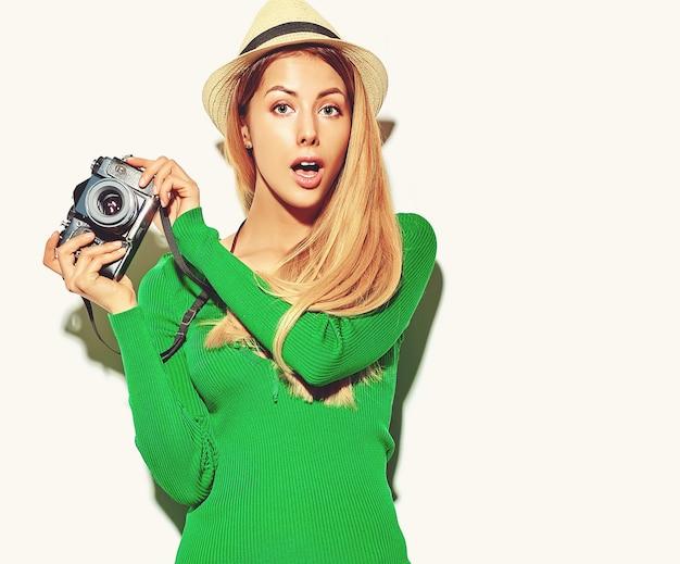 カジュアルな夏の緑のヒップスターの服で美しい驚いて幸せなかわいい金髪の女性の女の子は、レトロな写真用カメラを保持している写真を撮る、 無料写真
