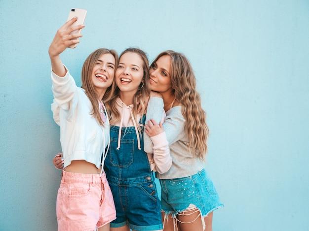 Три молодые улыбающиеся битник женщины в летней одежде. девушки, делающие фотографии автопортрета селфи на смартфоне. модели, позирующие на улице около стены. женщина, показывающая положительные эмоции лица. показывает язык Бесплатные Фотографии
