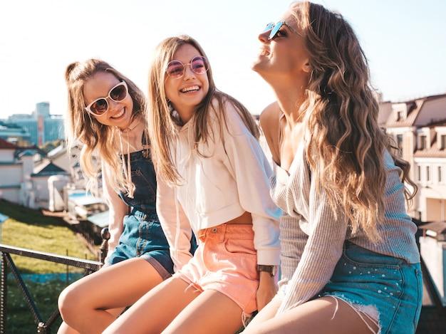 Сексуальные женщины сидят на перилах на улице они что-то общаются и обсуждают Бесплатные Фотографии