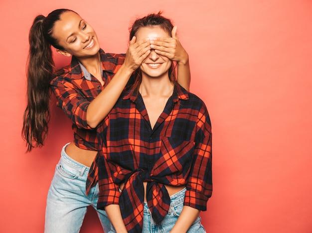 Две молодые красивые улыбающиеся брюнетки-хипстерские девушки в модной подобной клетчатой рубашке и джинсовой одежде. сексуальные беззаботные женщины, позирует возле синей стены в студии. Бесплатные Фотографии