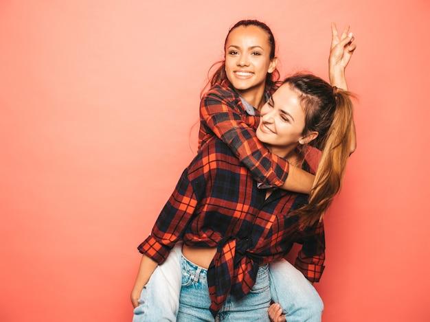 Две молодые красивые улыбающиеся брюнетки-хипстерские девушки в модной подобной клетчатой рубашке и джинсовой одежде. сексуальные беззаботные женщины позируют у розовой стены в студии. позитивная модель сидит на спине подруги Бесплатные Фотографии
