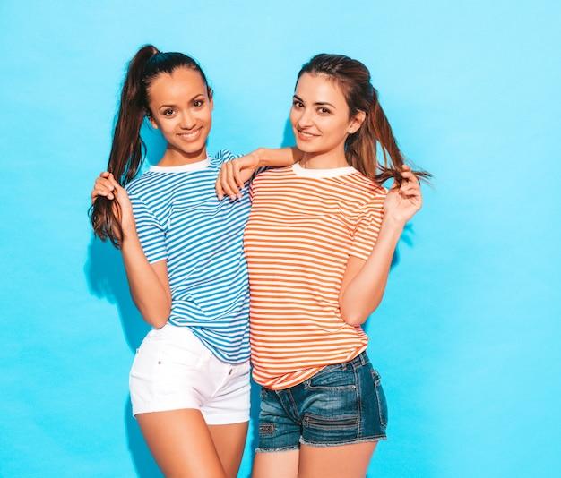Две молодые красивые улыбающиеся брюнетки-хипстерские девушки в модных похожих полосатых летних ярких рубашках. сексуальные беззаботные женщины, позирует возле синей стены в студии. позитивные модели с удовольствием Бесплатные Фотографии