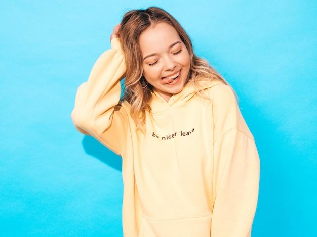トレンディな夏ヒップスター黄色パーカーの美しい笑顔少女の肖像画 無料写真