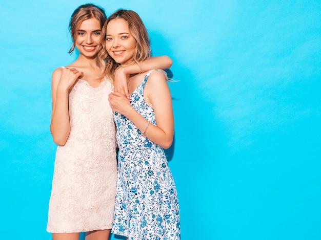 Две молодые красивые улыбающиеся хипстерские девушки в модных летних повседневных платьях. сексуальные беззаботные женщины позируют возле синей стены. веселиться и обниматься. модели показывают хорошие отношения. женщина без макияжа Бесплатные Фотографии