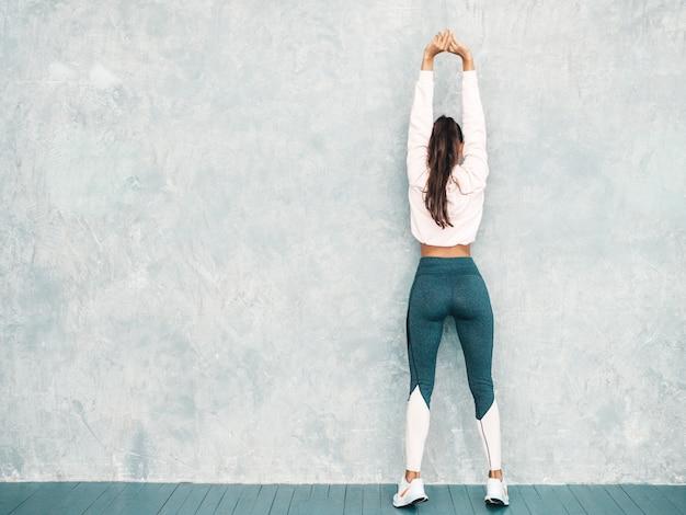 Задний взгляд женщины фитнеса в спортивной одежде смотря уверенно. женщина протягивая перед тренировкой около серой стены в студии Бесплатные Фотографии