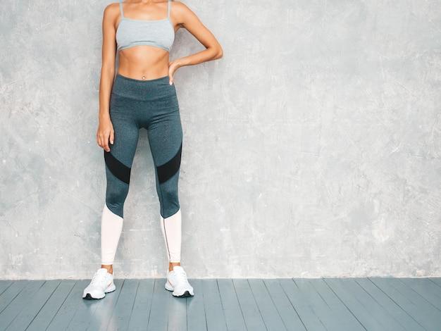 完璧な日焼けした体を持つ美しいモデル。灰色の壁の近くのスタジオでポーズをとる女性 無料写真