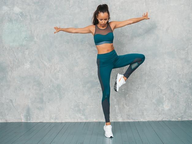 自信を持って探しているスポーツウェアのフィットネス女性の肖像画。スポーツウェアを着ている若い女性。完璧な日焼けした体を持つ美しいモデル。灰色の壁の近くのスタジオでジャンプする女性 無料写真