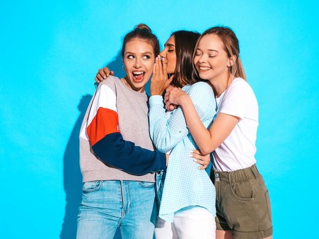 Сексуальные беспечальные женщины представляя около голубой стены в студии. позитивные модели сходят с ума и веселятся. делимся секретами, сплетничаем Бесплатные Фотографии