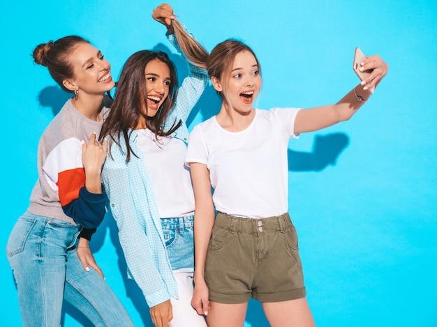 Девушки, делающие фотографии автопортрета селфи на смартфоне. модели, позирующие около синей стены в студии, женщина, показывающая положительные эмоции лица Бесплатные Фотографии