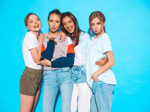 Сексуальные беспечальные женщины представляя около голубой стены в студии. позитивные модели развлекаются и обнимаются Бесплатные Фотографии
