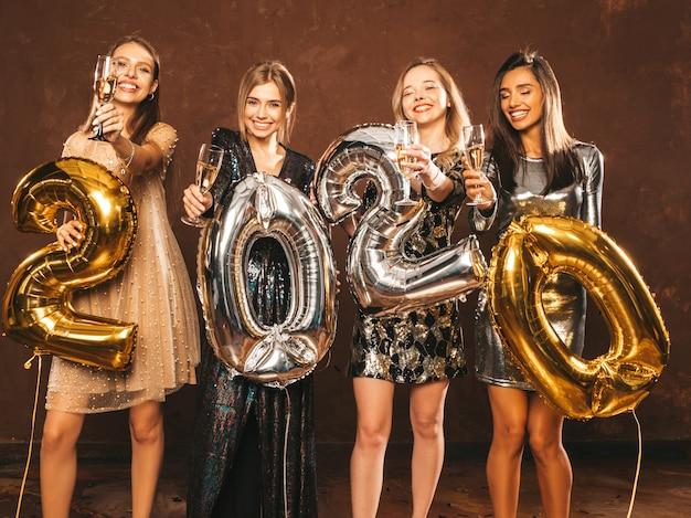Красивые женщины празднуют новый год. счастливые великолепные девушки в стильных сексуальных платьях Бесплатные Фотографии